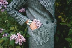 The young woman put a branch of lilac in her coat pocket. The delicate purple lilac in a femaly coat pocket. A lilac peeking out of female coat pocket.