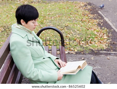 The young woman reads the book in autumn park