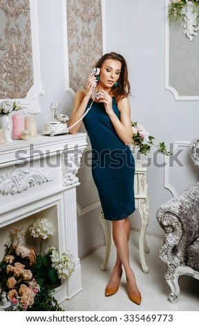 the young woman speaks by phone standing in an interior #335469773