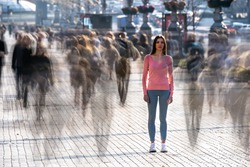 The young woman stands in the middle of crowded street