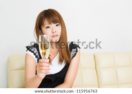 The young woman who drinks wine in a room