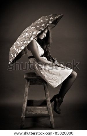 The young woman with an umbrella sits on a high stool - stock photo