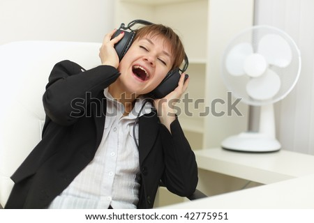 The young woman with ear-phones on a head sings on a workplace