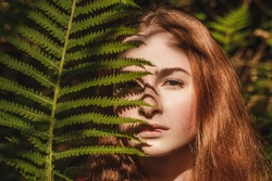 The young woman with fern leaf and shadow on face. Nature concept. Close up portrait.