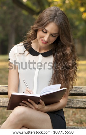 The young woman writes something in her book