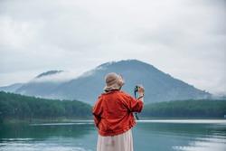 The young women take a photo at the beautiful view at the lake.Tuyen Lam Lake , Dalat , Vietnam