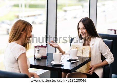 The young women with shopping bag in the cafe