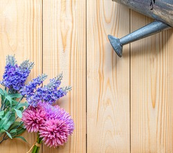 The zinc watering can is Watering water the violet Artificial lavender flowers of Plastic with purple slip flower and an orange board background And there is a copy space