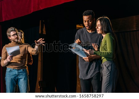 theater director, multicultural actors and actress rehearsing on stage