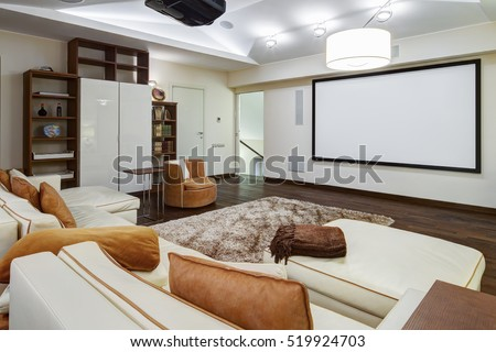 Theater room in luxury home with white big leather sofa and chairs #519924703