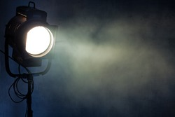 theater spot light with smoke against grunge wall