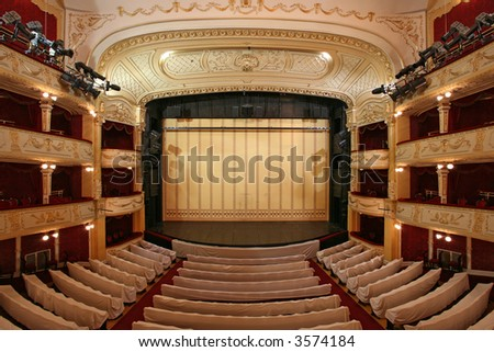 Theater stage with gold safety curtains and  empty chairs in the foreground