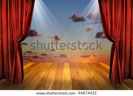 Theater stage with red curtains and spotlights on the stage wooden floor. Theatre interior with decorations of the dramatic sky wallpaper.