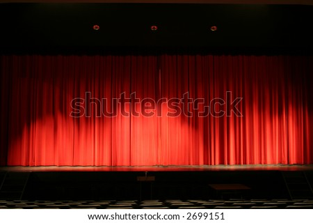 Theater stage with red velvet curtains and empty chairs in the foreground