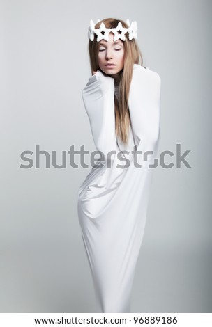 Theatre scene - young female posing in white crown over grey background in dramatic pose