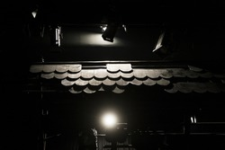 Theatrical stage with detailed scenography and spot light shining on it, black and white