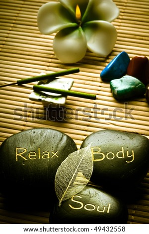 thee massage stones - relax, body, soul - and candle, aroma sticks and healing stones like a concept for wellness, body care, reiki and yoga symbols