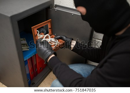 theft, burglary and people concept - thief in mask stealing valuables from safe at crime scene
