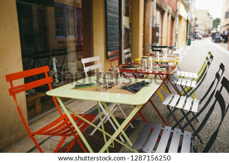 Theme cafes and restaurants. Exterior summer terrace of bright colors of street cafe shop in Europe in France. Preserved tables Without people, at tables nobody. #1287156250