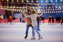 Theme ice skating rink and loving couple. meeting young, stylish people ride by hand in crowd on city skating rink lit by light bulbs and lights. Ice skating in winter for Christmas on ice arena.