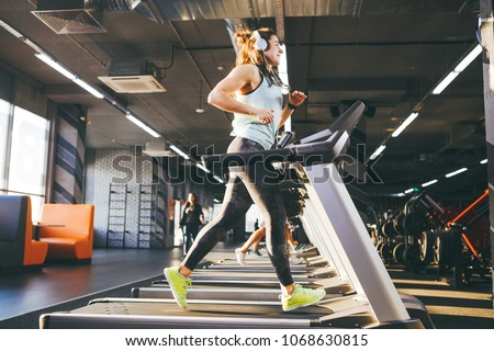 Theme is sport and music. A beautiful inflated woman runs in the gym on a treadmill. On her head are big white headphones, the girl listens to music during a cardio workout for weight loss.