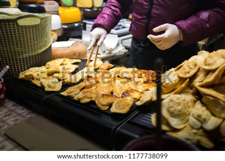 Theme is traditional street food in a European city on the market square in the Czech Republic Prague in the New Year's Eve, Christmas Eve festivities. Hands sell, prepare smoked cheese. #1177738099