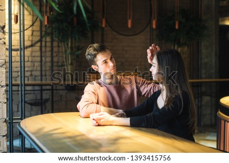 Theme love and holiday Valentines Day. couple of college students together in Caucasian heterosexual lovers winter inside the cafe sit at empty table embrace. Emotion happiness and love. #1393415756