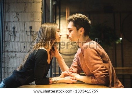 Theme love and holiday Valentines Day. couple of college students together in Caucasian heterosexual lovers winter inside the cafe sit at empty table embrace. Emotion happiness and love. #1393415759