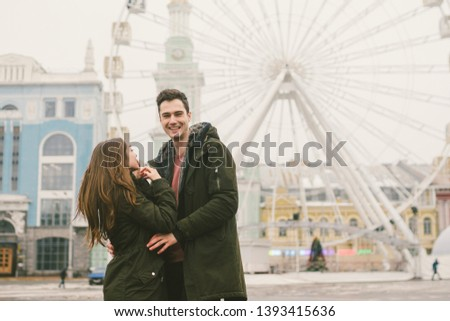 Theme love and holiday Valentines Day. pair of Caucasian heterosexual lovers in winter together gloomy weather embrace against background of Ferris wheel in town square. The guy gently hugs the girl. #1393415636