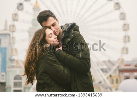 Theme love and holiday Valentines Day. pair of Caucasian heterosexual lovers in winter together gloomy weather embrace against background of Ferris wheel in town square. The guy gently hugs the girl. #1393415639