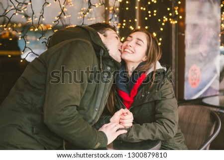 Theme love holiday Valentines Day. pair college students, Caucasian heterosexual lovers in winter, sit table of street cafe against the background window lights. Emotion romance of happiness and love. #1300879810