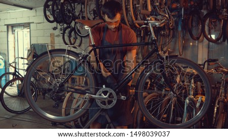theme small business bike repair. young Caucasian brunette man wearing safety goggles, gloves and apron uses hand tool repairing and adjusting crank and pedal system bicycle in the garage workshop.