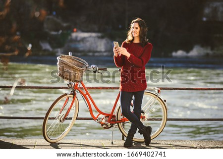 theme tourism on bicycle and modern technology. Beautiful young caucasian woman stands near red retro bicycle on riverside river Rhine Basel Swiss winter warm sunny weather uses the phone in hand. Stok fotoğraf ©