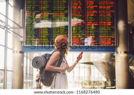 Theme travel and tranosport. Beautiful young caucasian woman in dress and backpack standing inside train station or terminal looking at a schedule holding a red phone, uses communication technology. Сток-фото ©