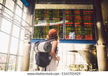 Theme travel public transport. young woman standing with back in dress and hat behind backpack and camping equipment for sleeping, insulating mat looks schedule on scoreboard airport station sunny day