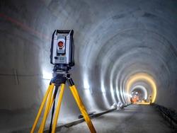 Theodolite at underground railway tunnel construction work. Construction survey equipment instrument on concrete circular tunnel background.
