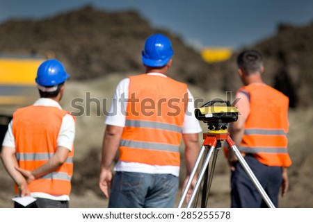 Theodolite on tripod at road construction site with workers supervising works
