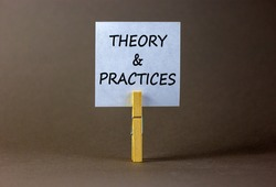 Theory and practice symbol. White paper with words 'Theory and practice', clip on wooden clothespin. Beautiful grey background. Business, theory and practice concept. Copy space.