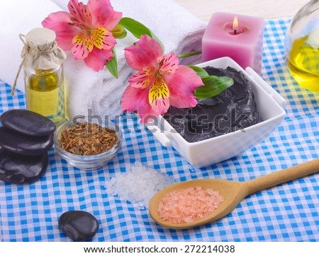 therapeutic black mud in the bowl on the birch table oil and stones to massage the petals and white towel blue napkin