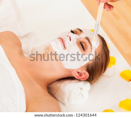 Therapist applying a face mask to the face of a beautiful young blonde woman using a cosmetic brush