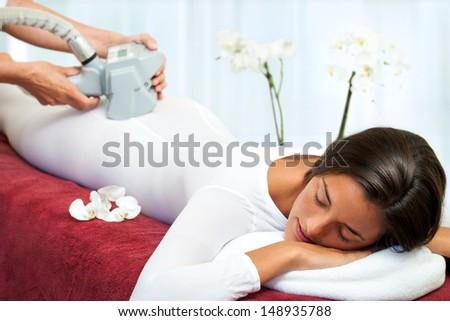 Therapist applying lipo massage on girls body in spa.