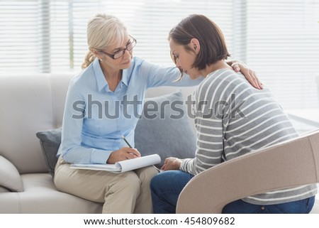 Therapist comforting woman on sofa at home