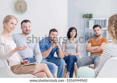 Therapist congratulating young woman on her progress in therapy and happy family in the background