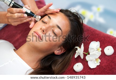 Therapist doing anti aging facial moisture infusion on woman.