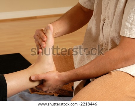 therapist giving a foot massage to client