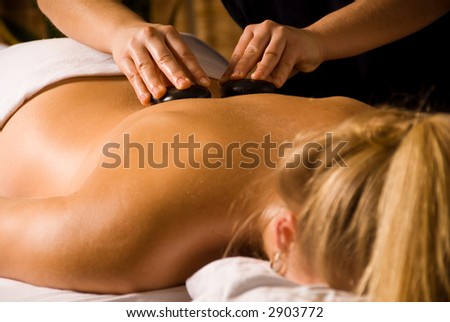 therapist giving a hot stone massage cute blond