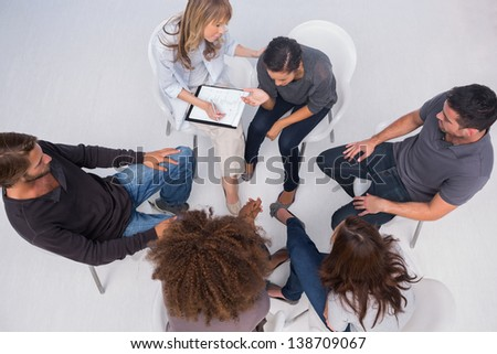 Therapist helping a patient during group therapy session
