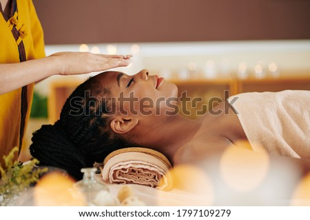 Therapist holding hands over head of pretty young Black woman to transfer energy during healing reiki session