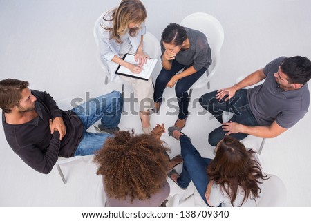 Therapist listening to patient during group therapy session