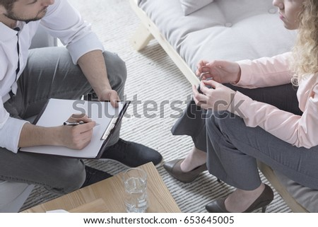 Therapist sitting in front of patient with paper and pen #653645005